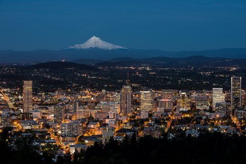 Picture of view of the city of Portland at night with the snow covered Mt. Hood in the distance